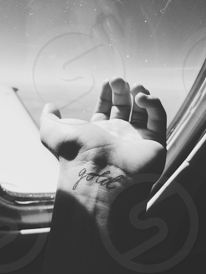 grayscale photography of left human hand with gold printed tattoo while riding on an airplane photo