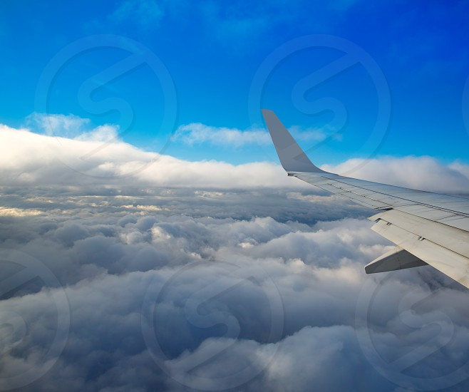 Aircraft wing flying over a sea of clouds and blue sky photo