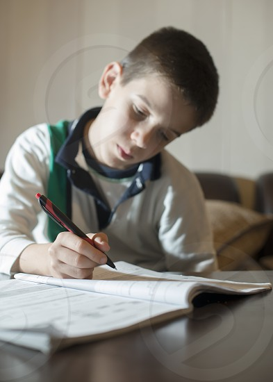 Child do his homework. Notebook for mathematic. Hand hold pen. Boy learning photo