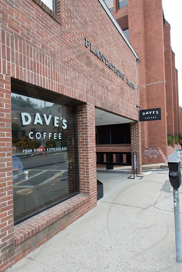 man in blue dress shirt sitting by the window inside the dave's coffee photo