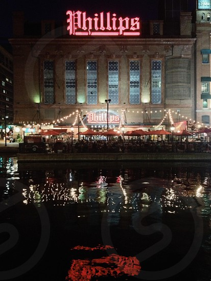 restaurants along the water Baltimore Inner Harbor. (water reflection neon sign lights night) photo