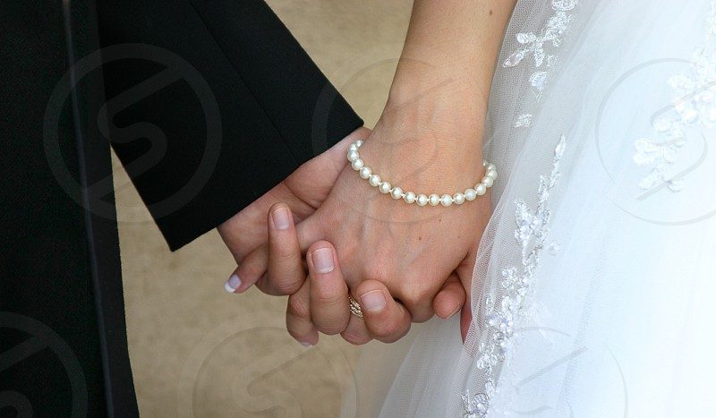 A young married couple holding hands. Tux dress gown black white yellow pearls manicure wedding bride groom photo