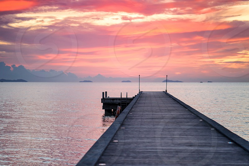 Sunset at lake Long wooden pier with the orange sky during sunset Golden sky Red sky with copy space photo