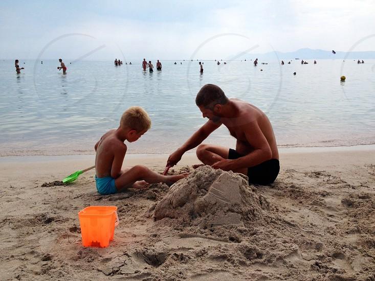 man and a boy on a sandy beach photo