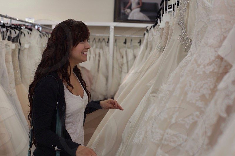 woman in black sweater and white shirt inside wedding gown shop photo