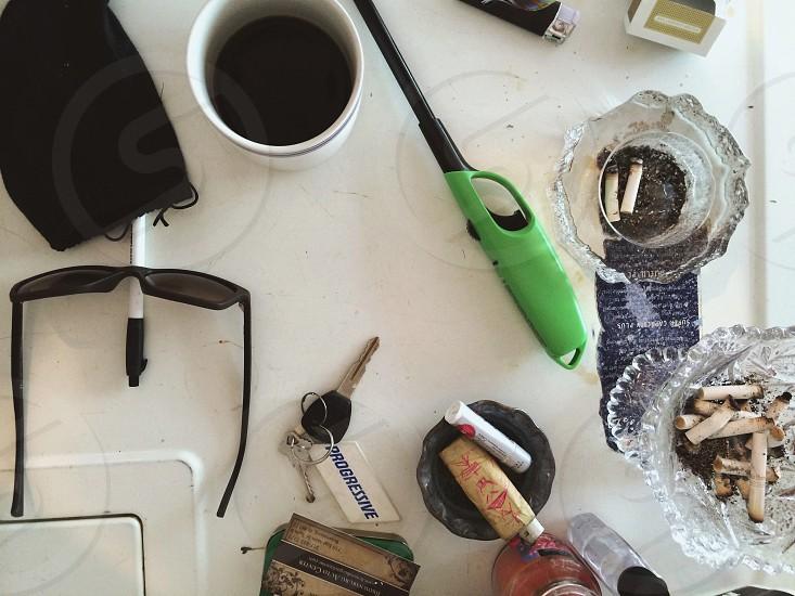 green kitchen lighter near clear glass ashtray photo
