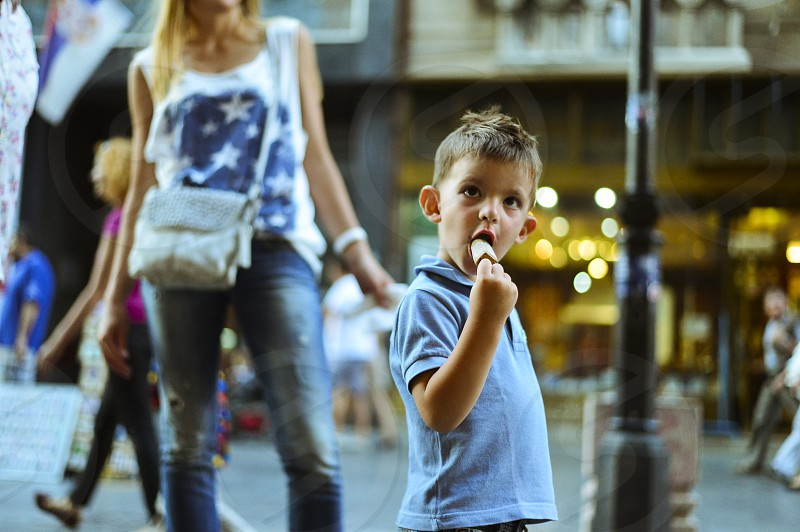 boy in blue polo shirt holding ice cream selective focus photography photo