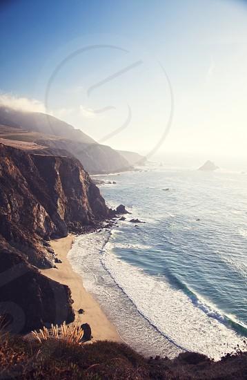 beach near a brown rocky mountain cliff  photo