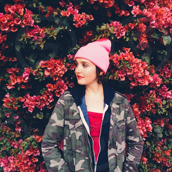 woman in pink beanie standing in front of wall of flowers photo