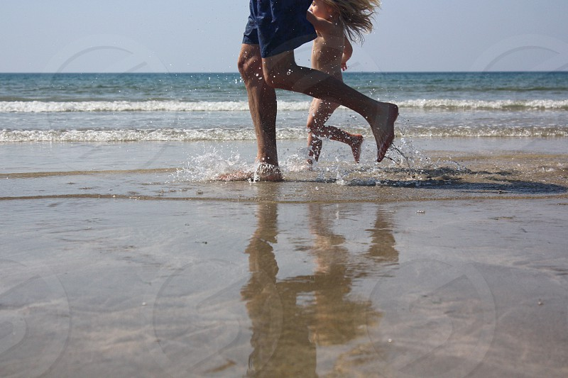 Father and daughter running through the sea photo