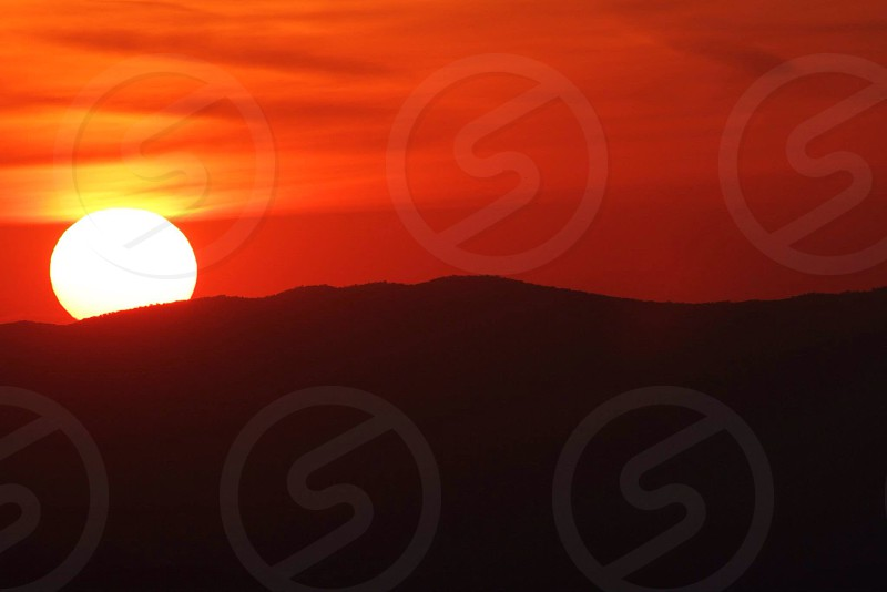 sun setting over hill with red sky photo