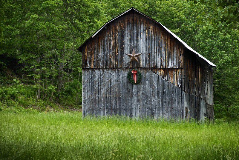 An old weathered barn with a holiday wreath sits in a grass field. photo