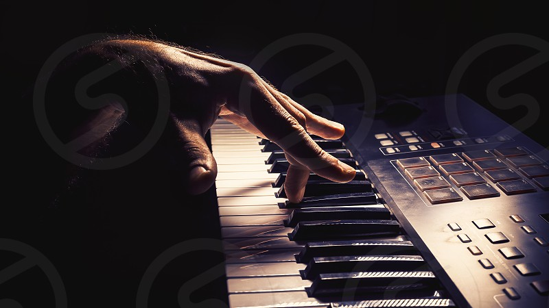 Playing a keyboard left hand act accentuated contrasts.   photo