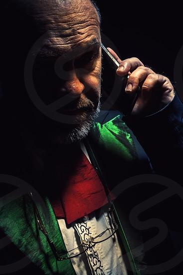 Studio portrait of an older beard man looks like an artist conductor or something similar.  photo