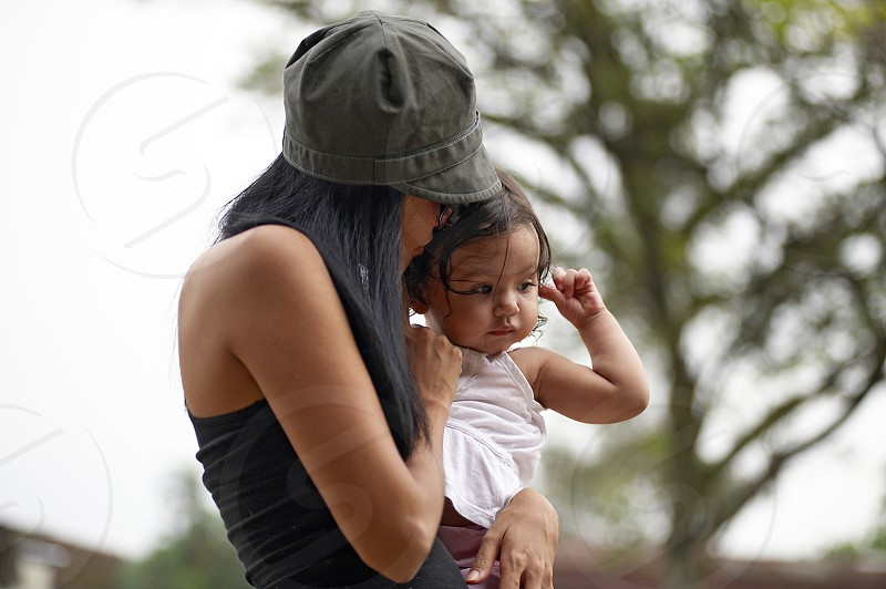 Young Asian mother carrying her little baby girl outside in the park in summer sunshine photo