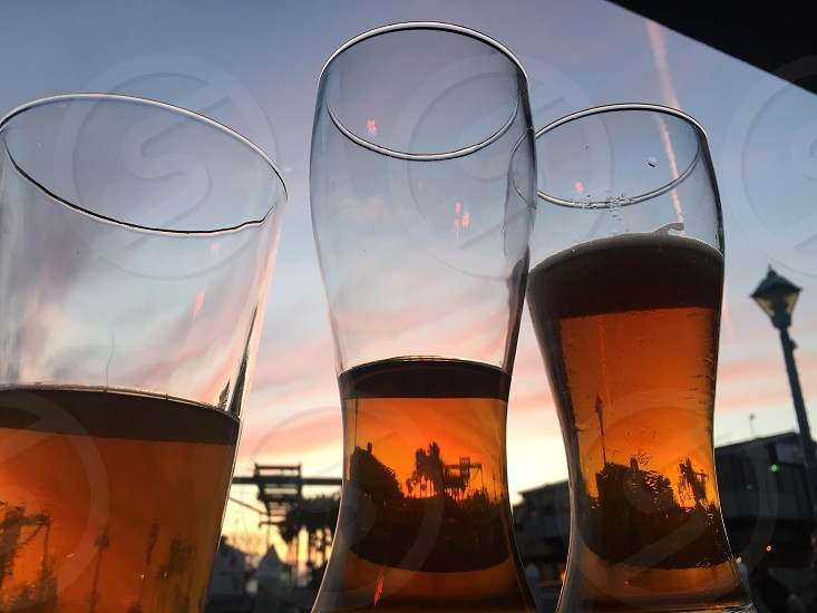 2 clear weizen glasses beside clear highball glass with beers photo