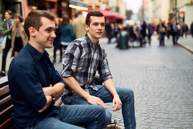 Two man sit on bench and talk on the street  photo