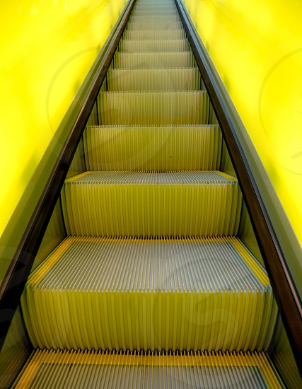 low angle photo of grey and yellow escalator steps photo