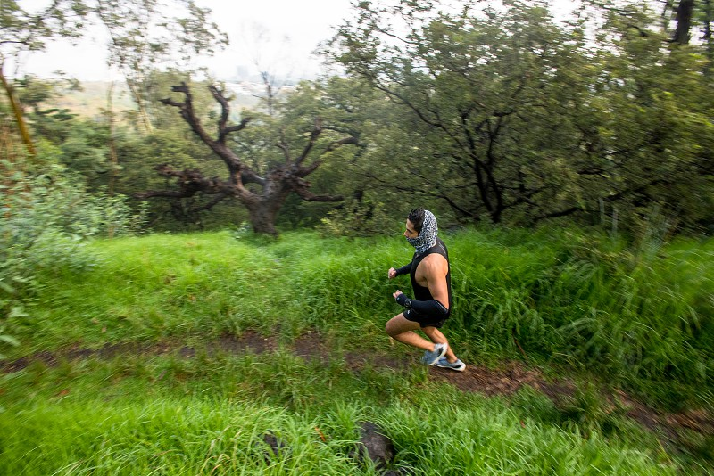 Young man having an early morning run in a forest in Mexico photo