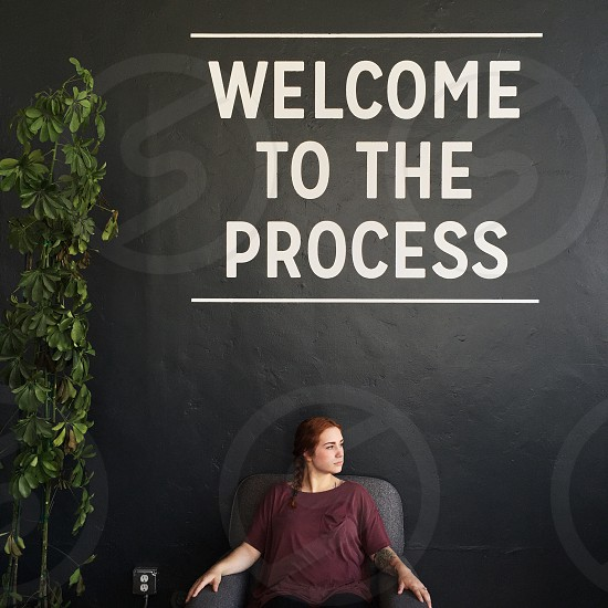 woman in maroon t shirt sitting on gray armchair in front of welcome to the process signage during daytime photo