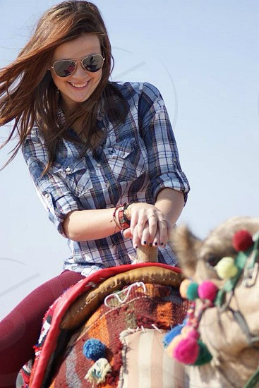 woman in gray and white plaid sports shirt smiling while riding camel photo