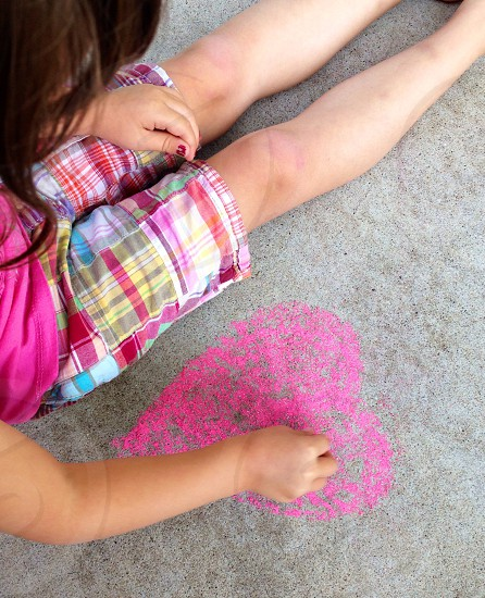 girl drawing heart on sidewalk photo