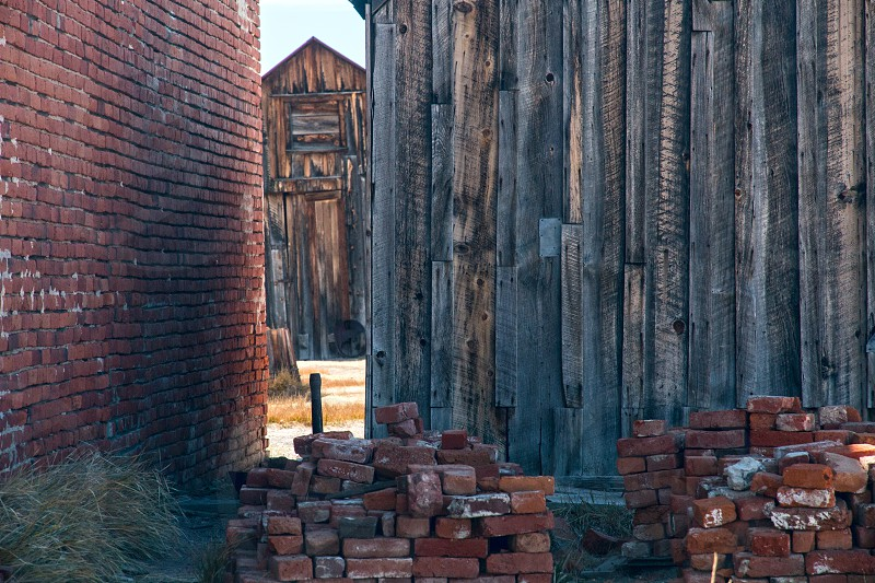 brown brick building and gray wooden building near brown bricks on ground photo