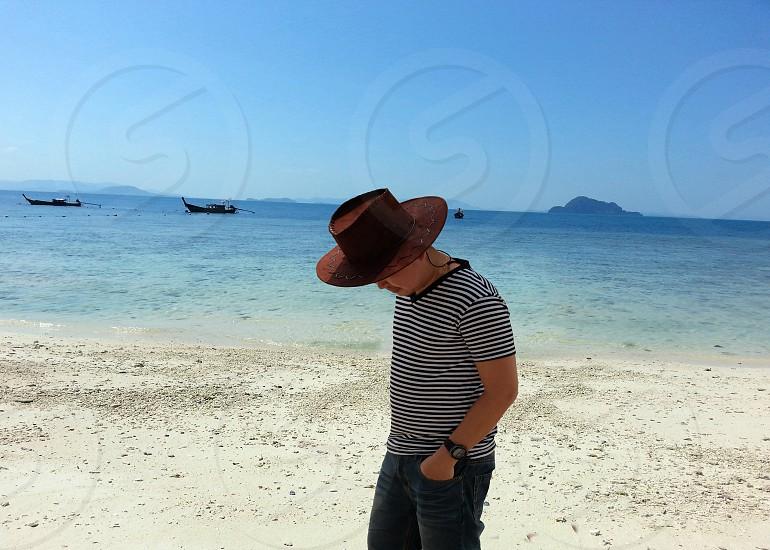 man in gray and black stripe shirt blue denim jeans and brown cowboy hat walking beige seashore near blue ocean under blue sky photo