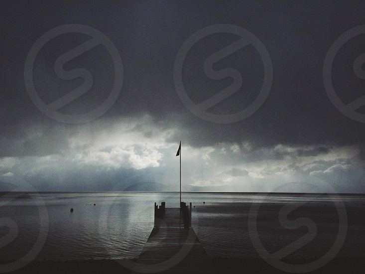 Storm over lake with pier photo