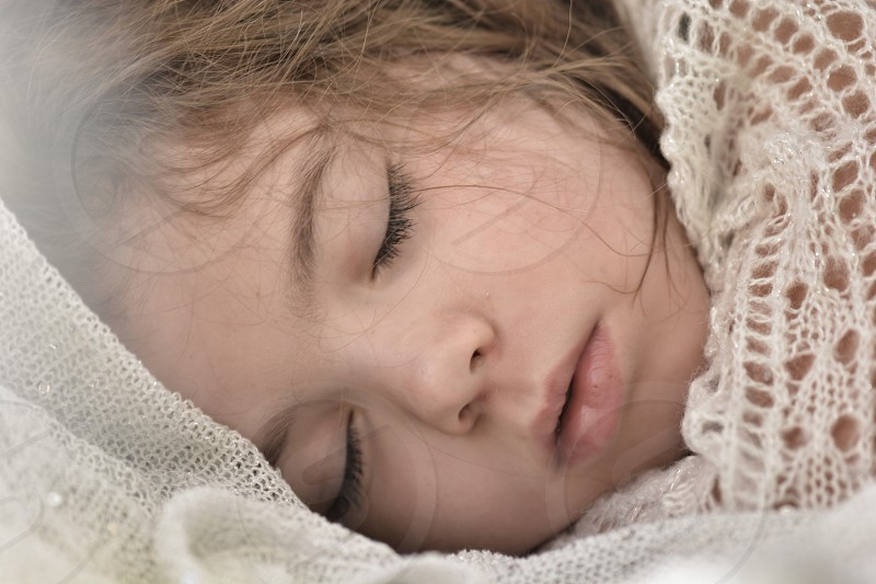 close up photo of girl sleeping covered in white knitted cloth photo