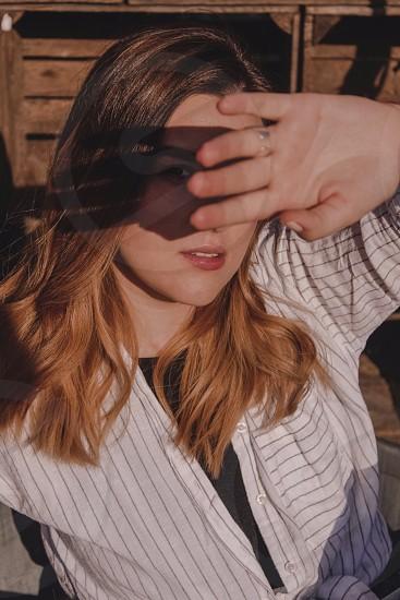 Girl sun covering face closeup photo