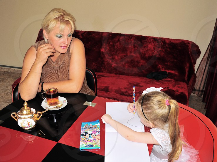 woman sitting leaning on table watching girl writing on white paper photo