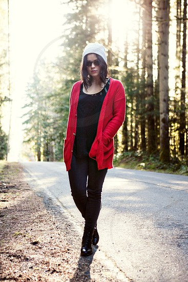 woman in black shirt and red cardigan standing on road photo
