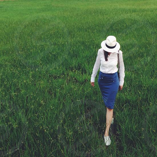 woman wearing a white fedora hat walking across a green field photo