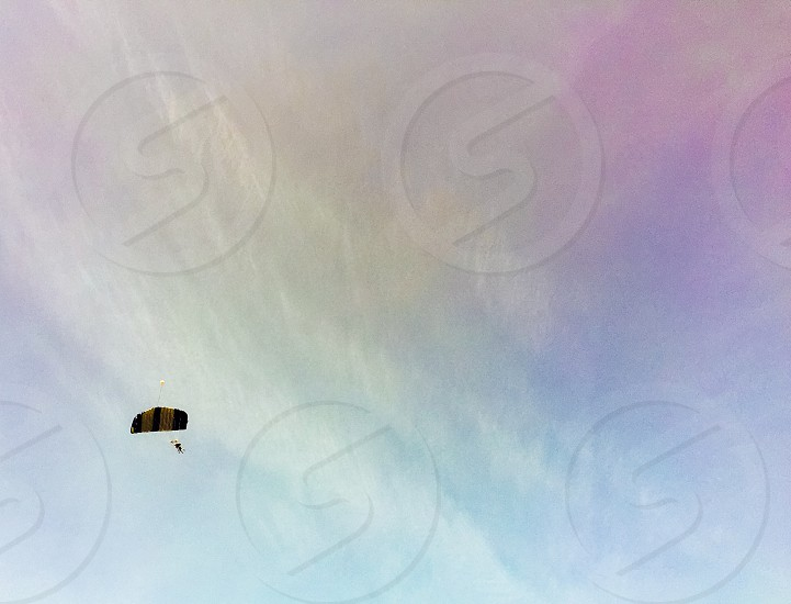 blue pink white cloudy sky with one parachutist photo