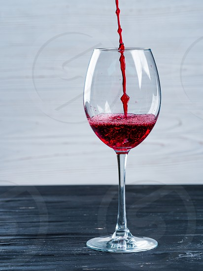Red wine being poured into wine glass on white background. Minimalist style black shabby vintage wooden table. photo