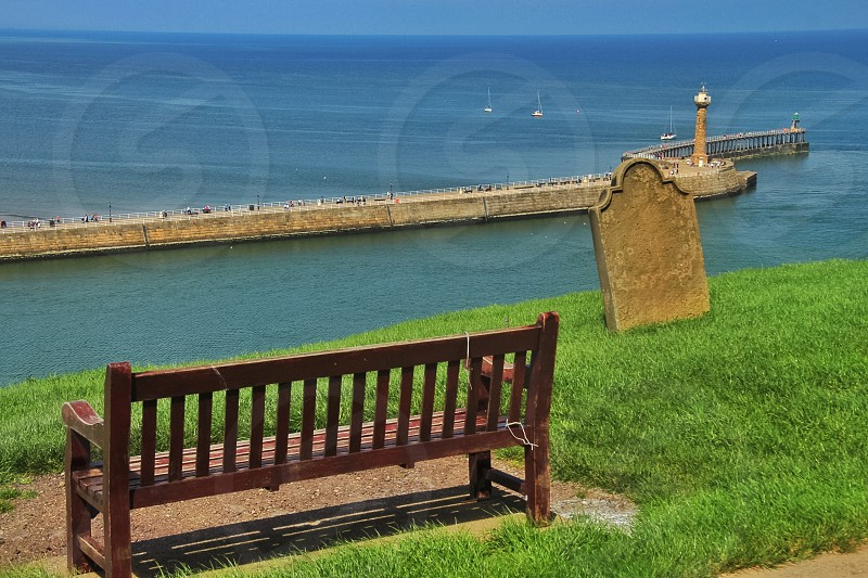 concrete bridge with light house on the edge bench  and green grass photo