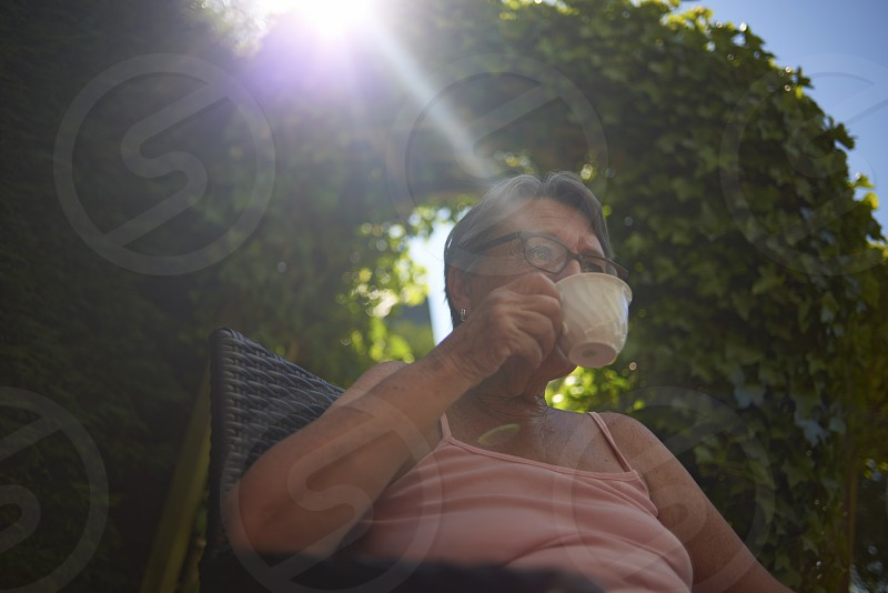 Affluent elderly woman sitting in her back garden enjoying the summer sunshine drinking coffee photo