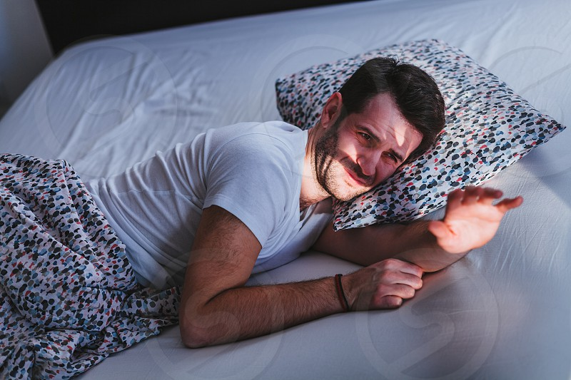Young tired man waking up in bed in the morning photo