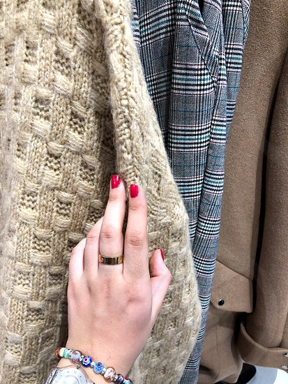 Shopping. Choice of clothes.  Hand of a young girl with a ring  photo