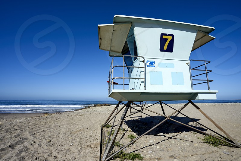 Lifeguard tower # 7 against pretty blue morning sky with sea behind it photo
