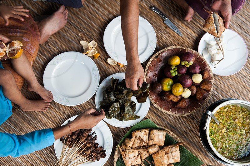Overhead view of Balinese family sitting and reaching for food at dinner photo