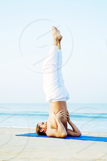 Long Hair Athletic Man with No Shirt doing Yoga on Blue Mat at the Beach photo