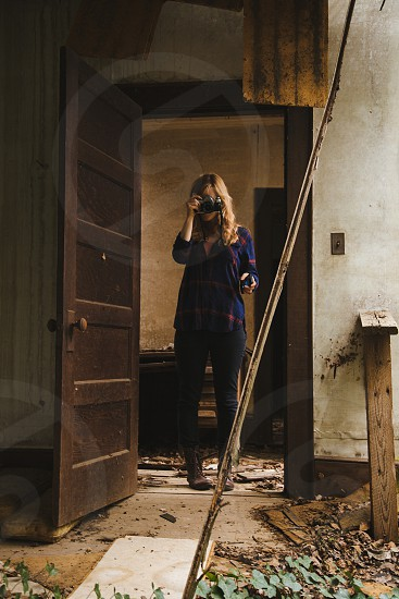 woman standing near brown door holding black camera photo
