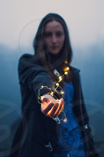Portrait of a girl in the morning holding yellow fiary lights. photo