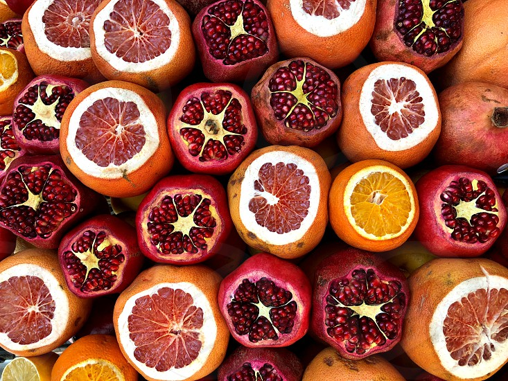 Sliced pomegranates and oranges.  Natural fruits natural vitamins. A living fragment from a fruit and vegetable store. photo
