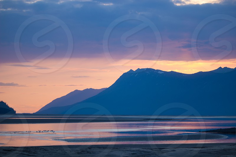 mountain on seaside under grey clouds photo