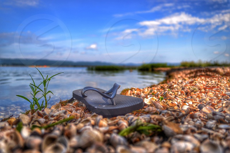 black flip flop on pebbled ground photo