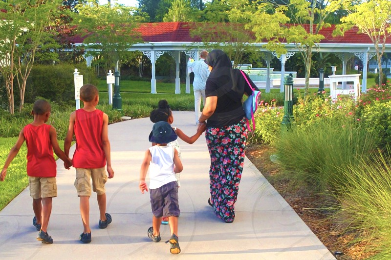 woman wearing black hijab walking with her child wearing white tank top while the other two are wearing red tank top walking on grey concrete pathway while holding hands during daytime photo