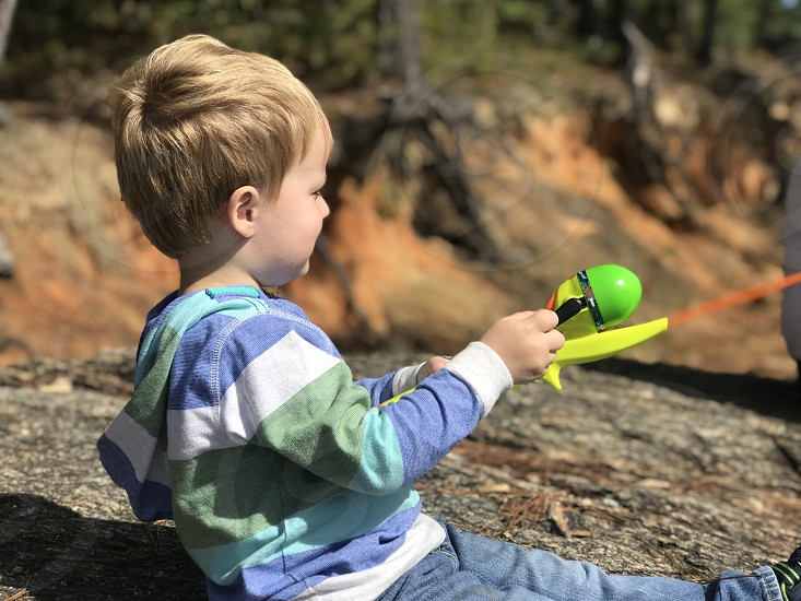 Little boy toddler fishing fishing pole lake vacation rocks blue yellow green blonde photo